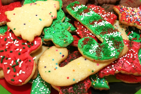 Red green and white Christmas cookies with sprinkles in a pile.